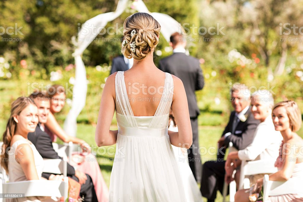 Bride Walking Down The Aisle During Wedding Ceremony stock photo