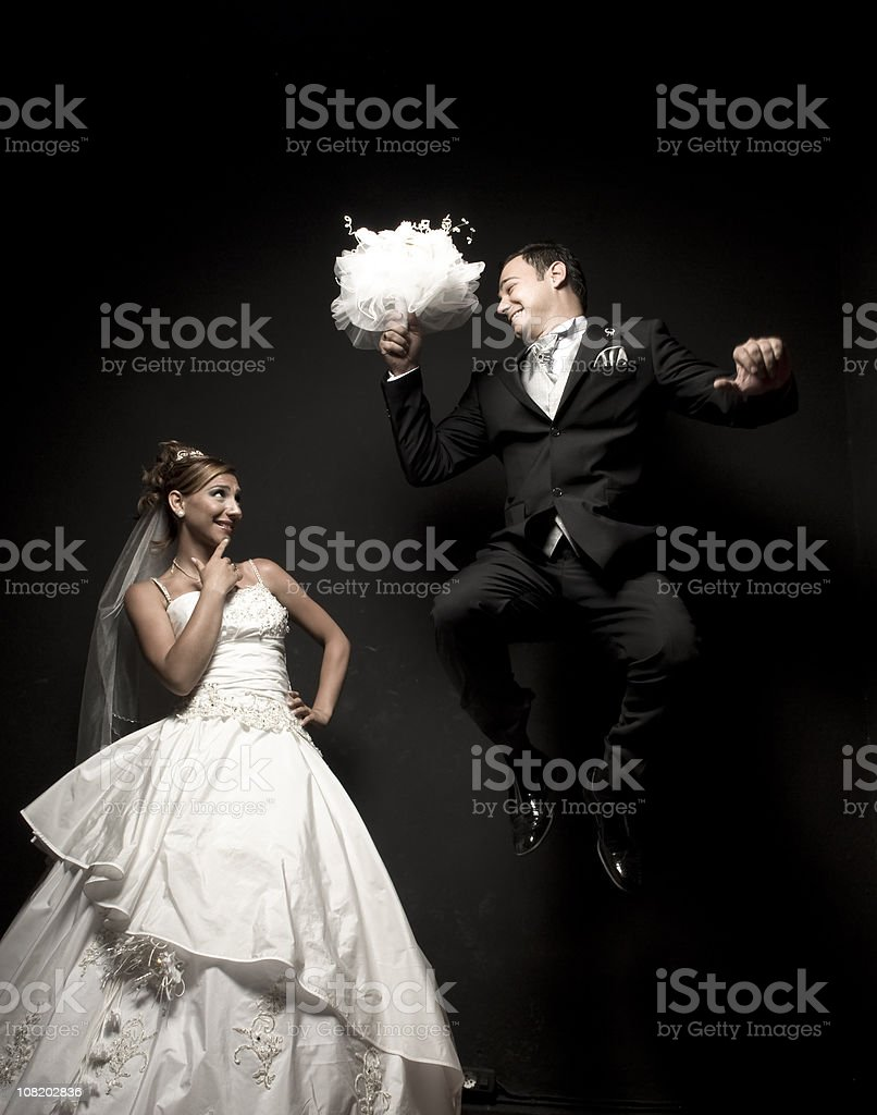 Bride Watching Happy Groom Jumping in Air royalty-free stock photo