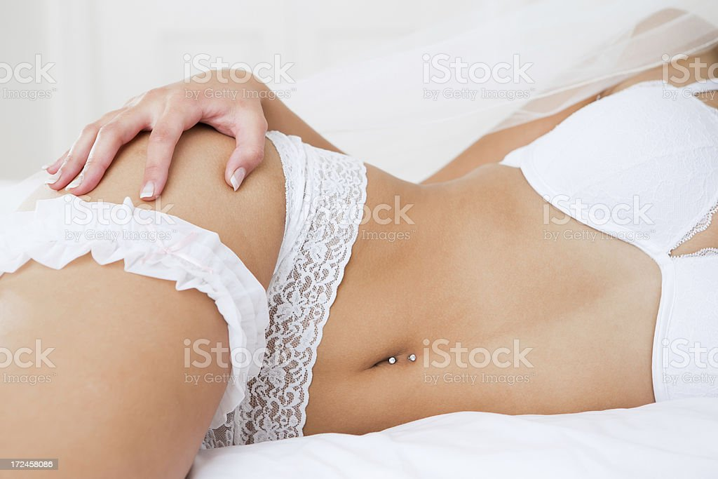 Bride wearing lingerie laying on bed royalty-free stock photo