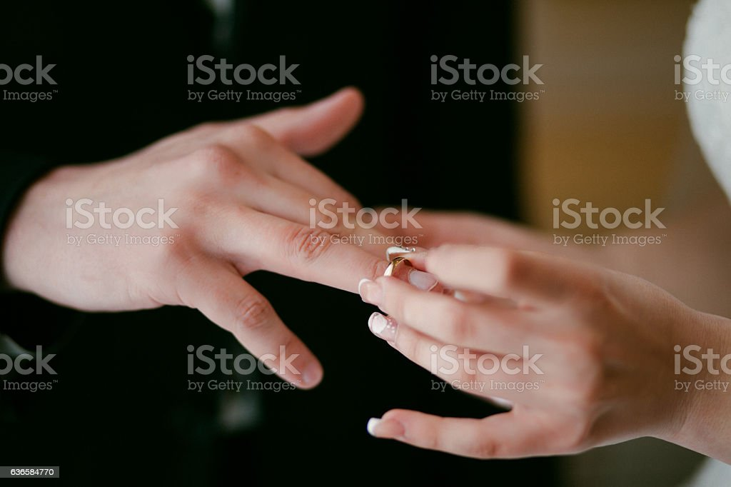 Bride wearing the Wedding Ring on groom. She Put the stock photo