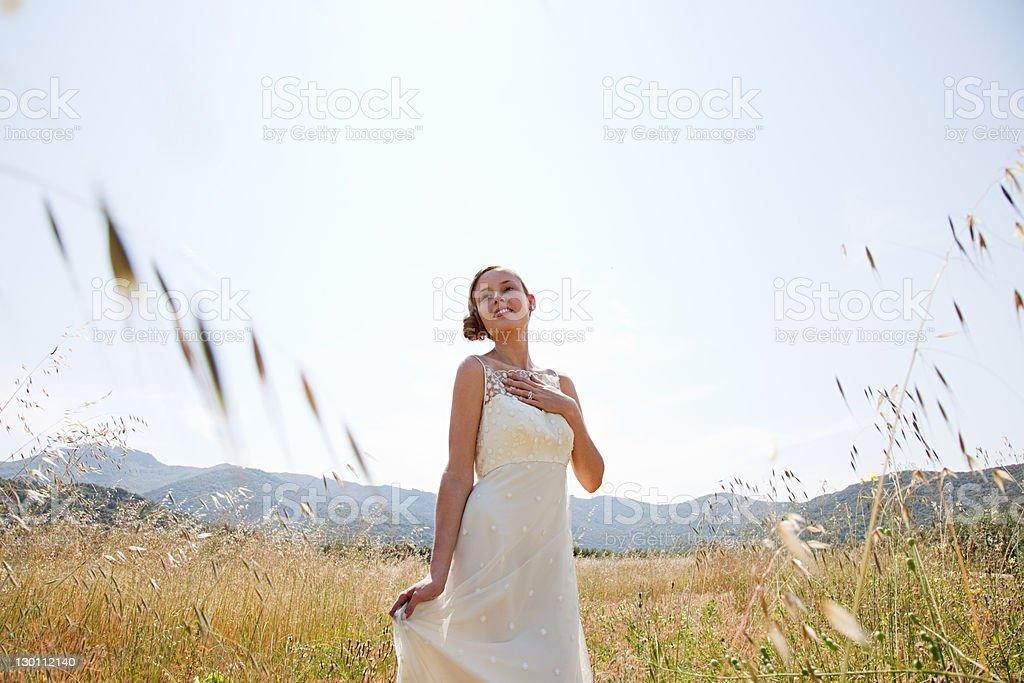 Bride wearing wedding dress alone in field stock photo