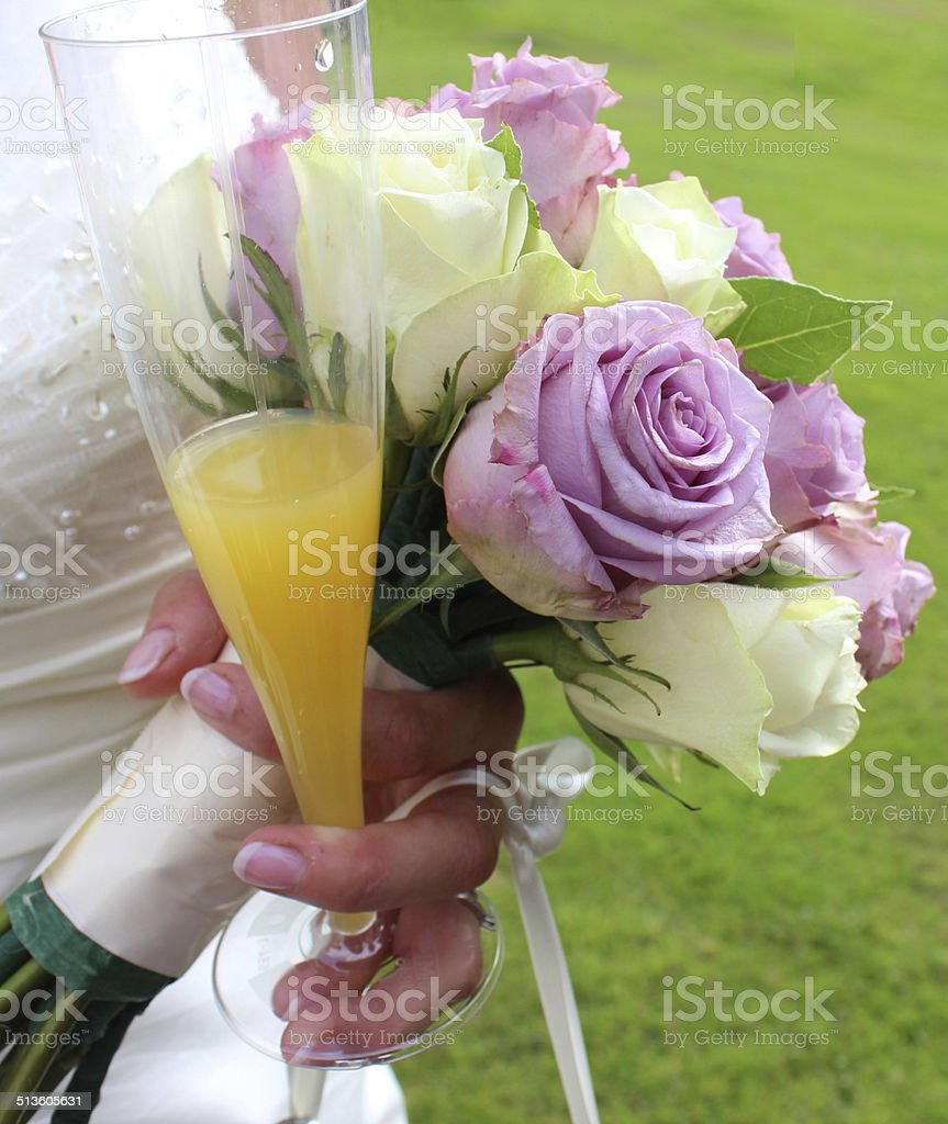 Bride wearing white wedding dress, bridal-bouquet, flowers, champagne glass, bucks-fizz stock photo