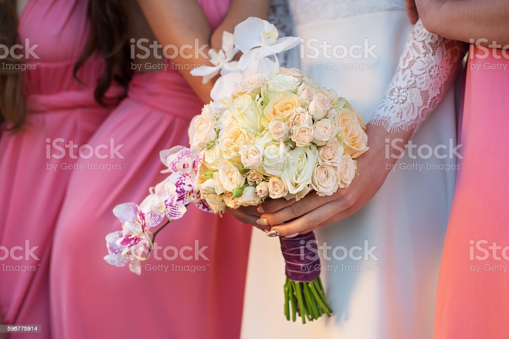 Bride with a bouquet in hand and girlfriends stock photo