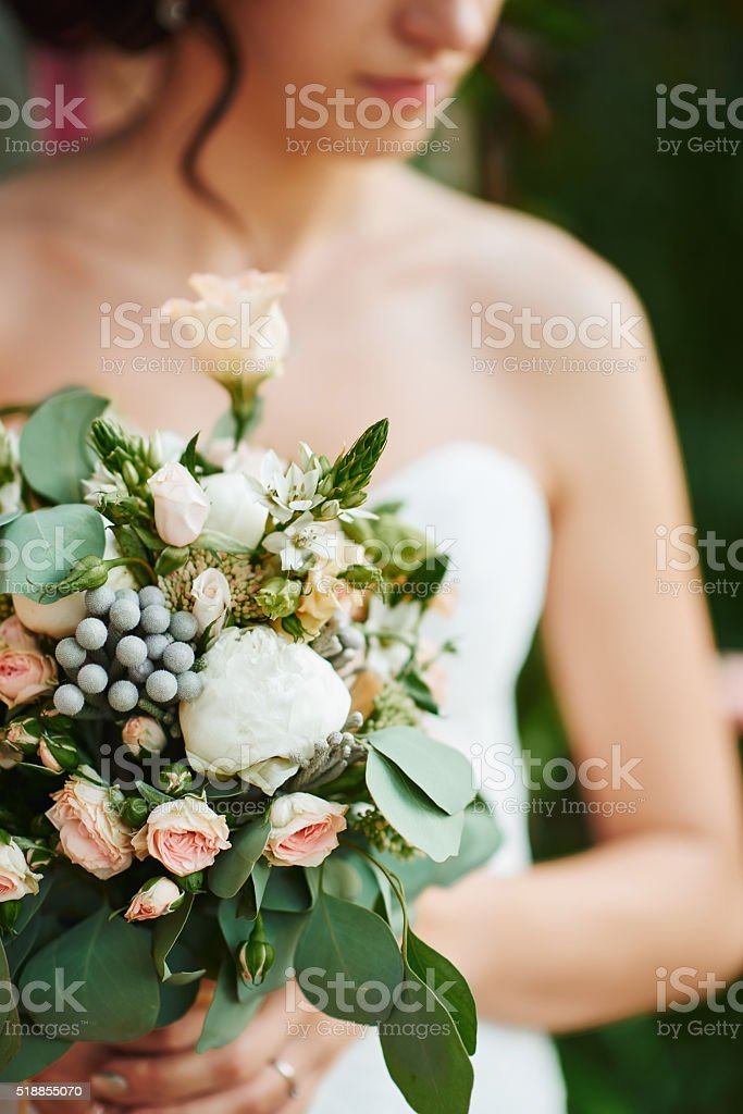 Bride with a wedding bouquet. Arch stock photo