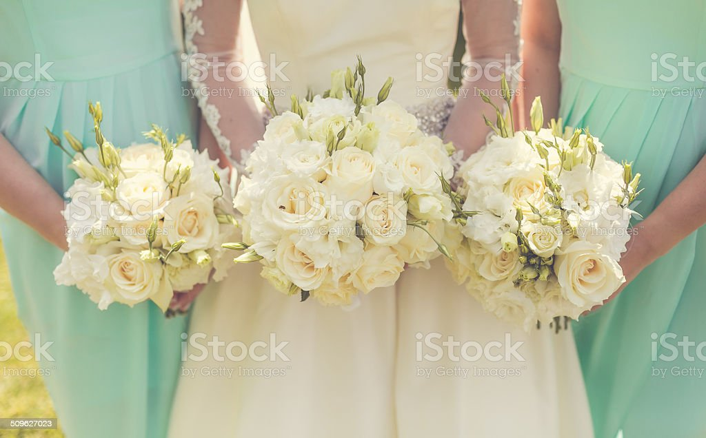 Bride with bridesmaids holding wedding bouquets stock photo
