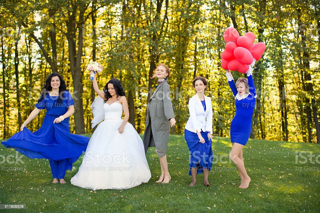 Bride with her friends dancing in the meadow stock photo