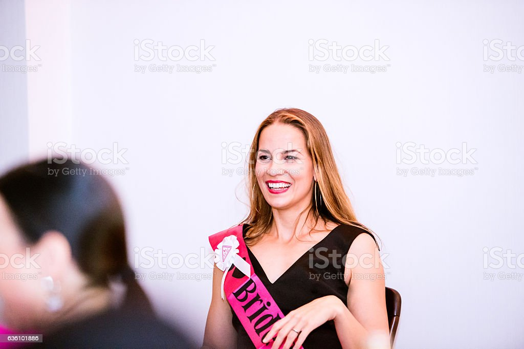 Bride with pink sash celebrating hen party with bridesmaids stock photo