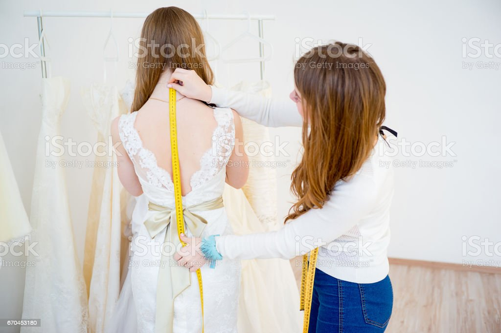 Bride with wedding assistant stock photo