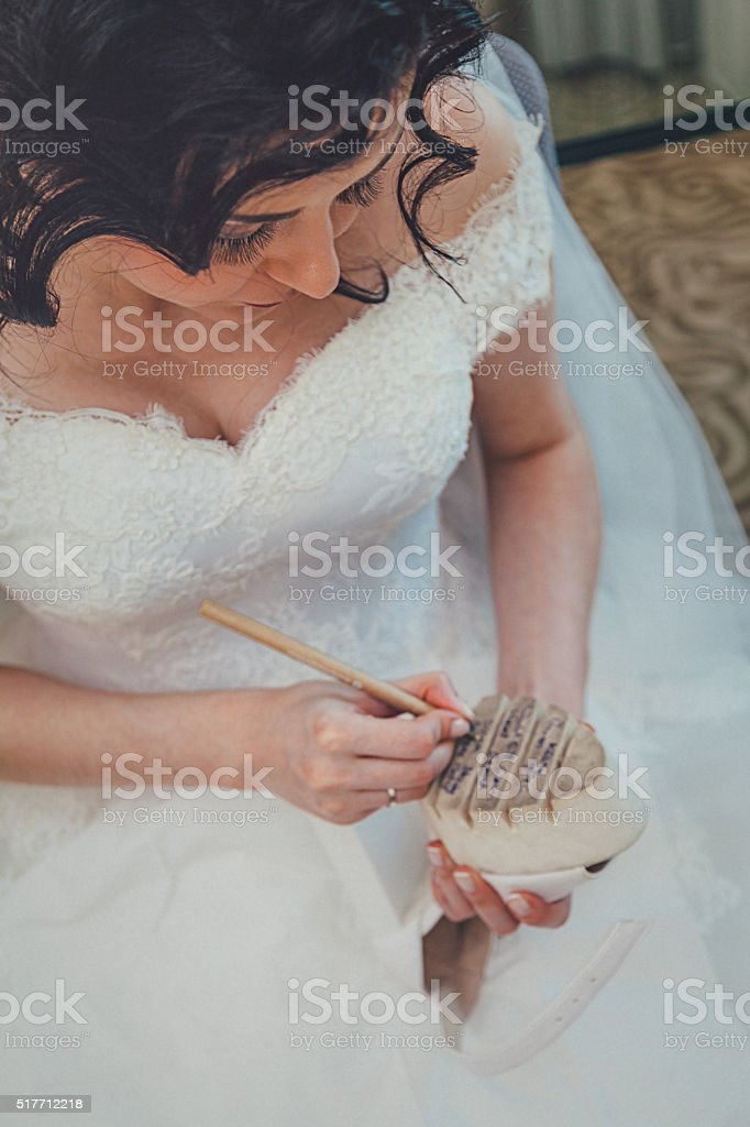 Bride writing names under the shoes stock photo