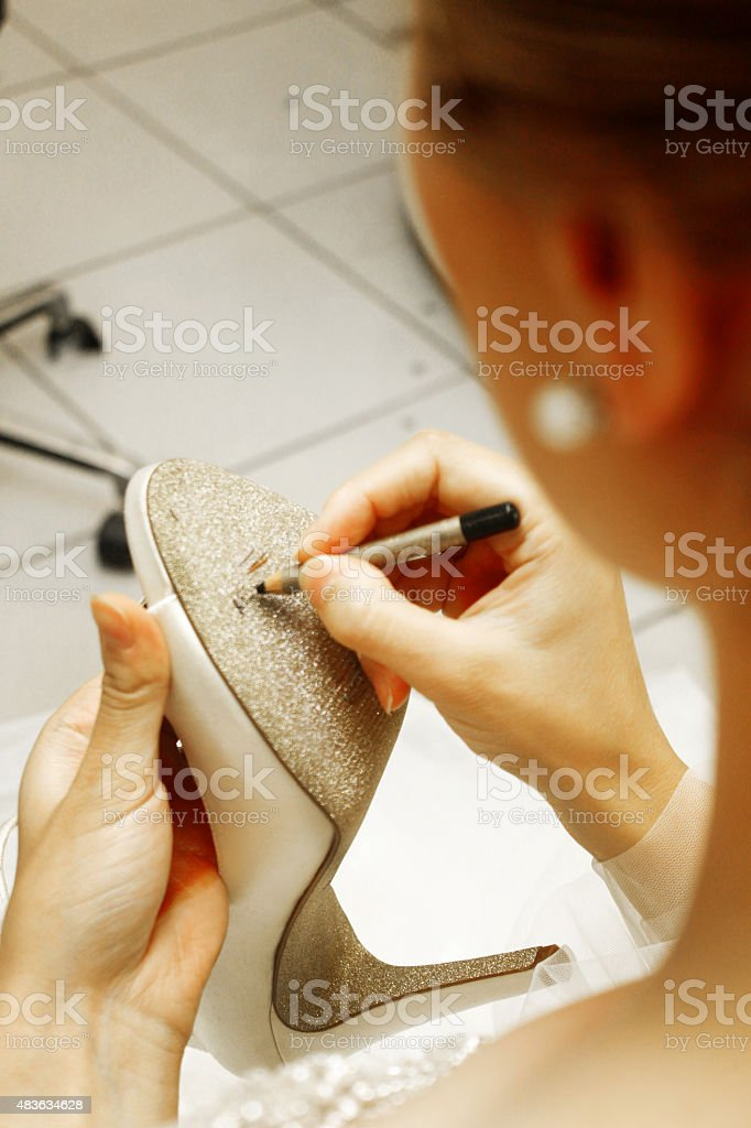 Bride writing names under the wedding shoes stock photo