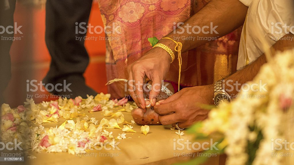 Bridegroom places ring on the brides toe stock photo