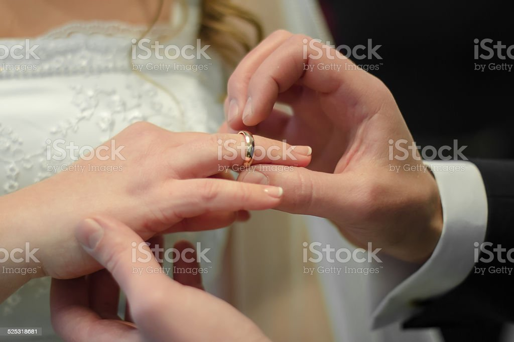 Bridegroom wears the ring to bride's finger stock photo