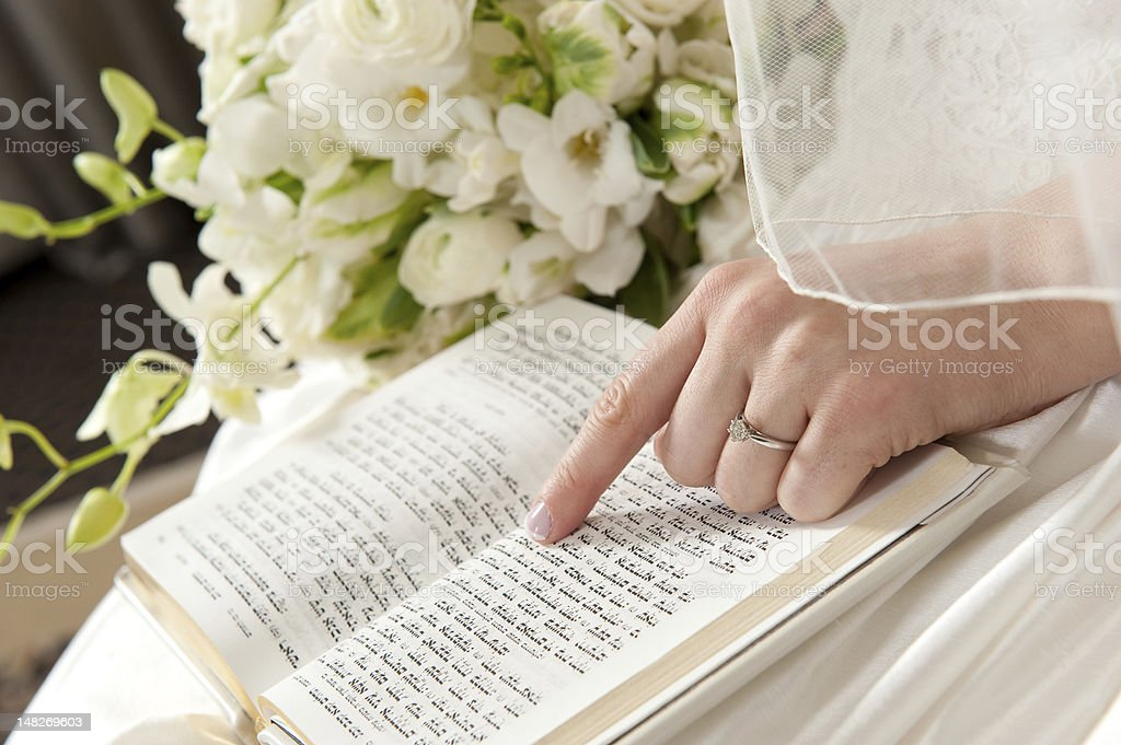 Bride's Hand on Prayer Book stock photo