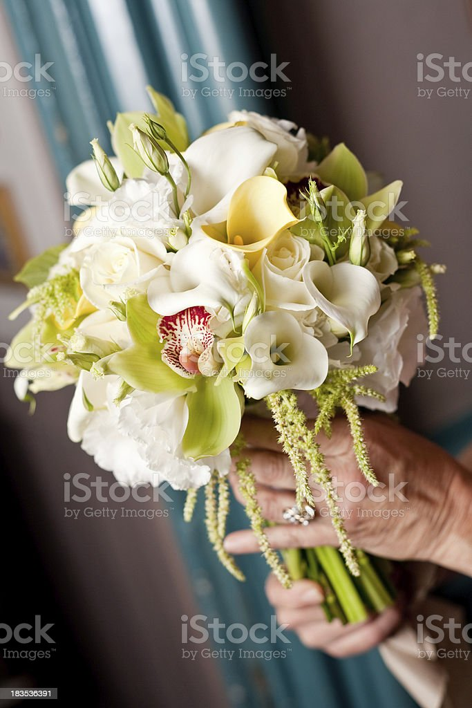 brides hands holding her floral bouquet wearing engagement ring stock photo
