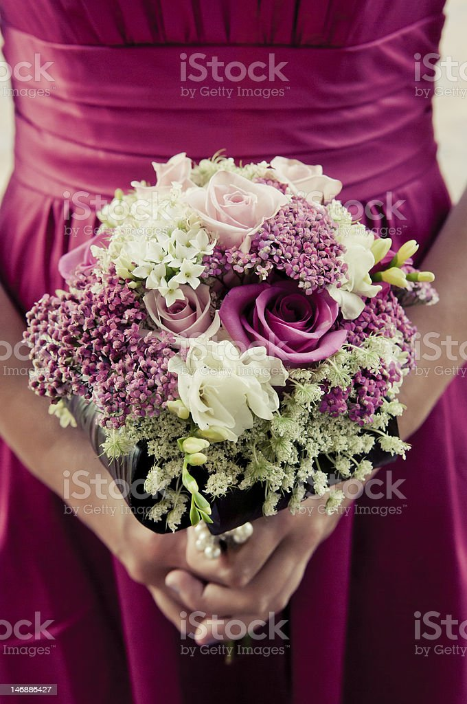 Brides maid in pink holds bouquet of flowers stock photo