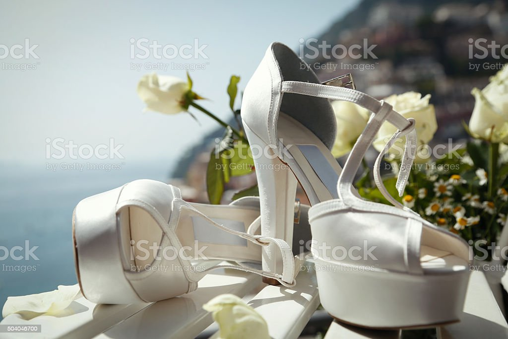 Bride's shoes and bouquet stock photo