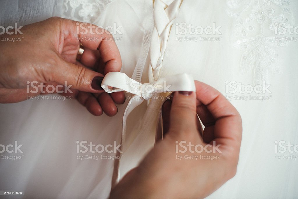 bridesmaid buttoning the dress on bride stock photo