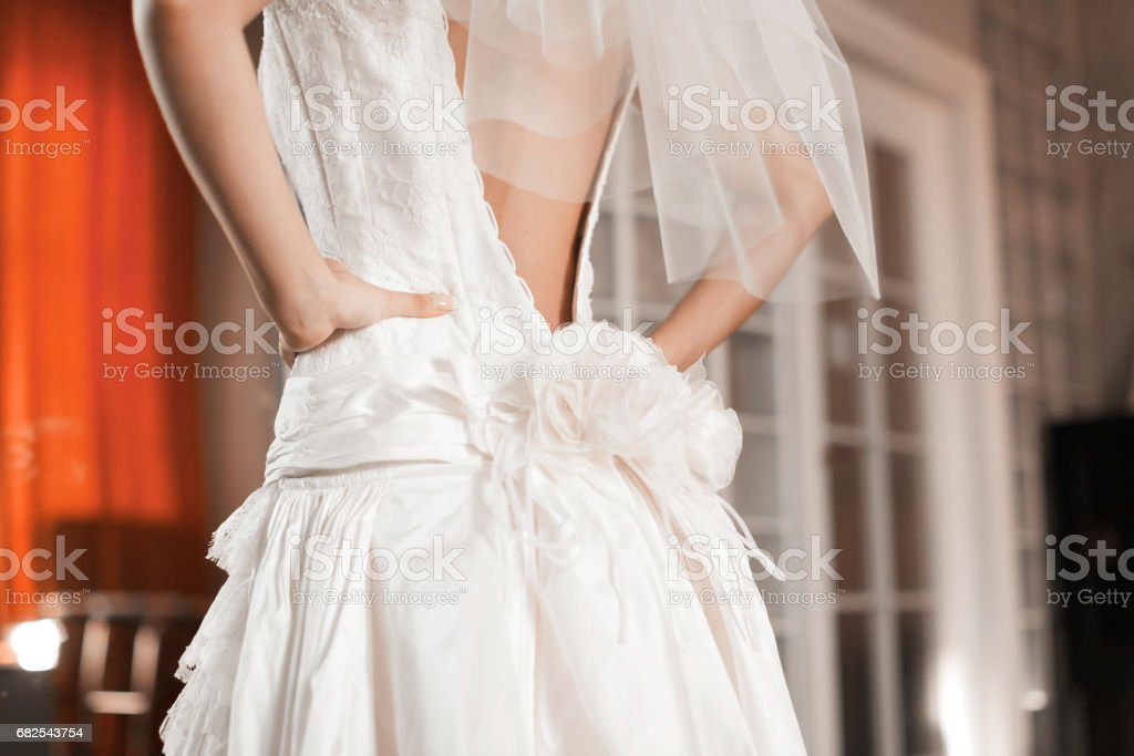 Bridesmaid dresses bride for the wedding day. Bridesmaid helps with a white dress before the ceremony. Luxury bridal dress close up. Best wed morning. concept stock photo