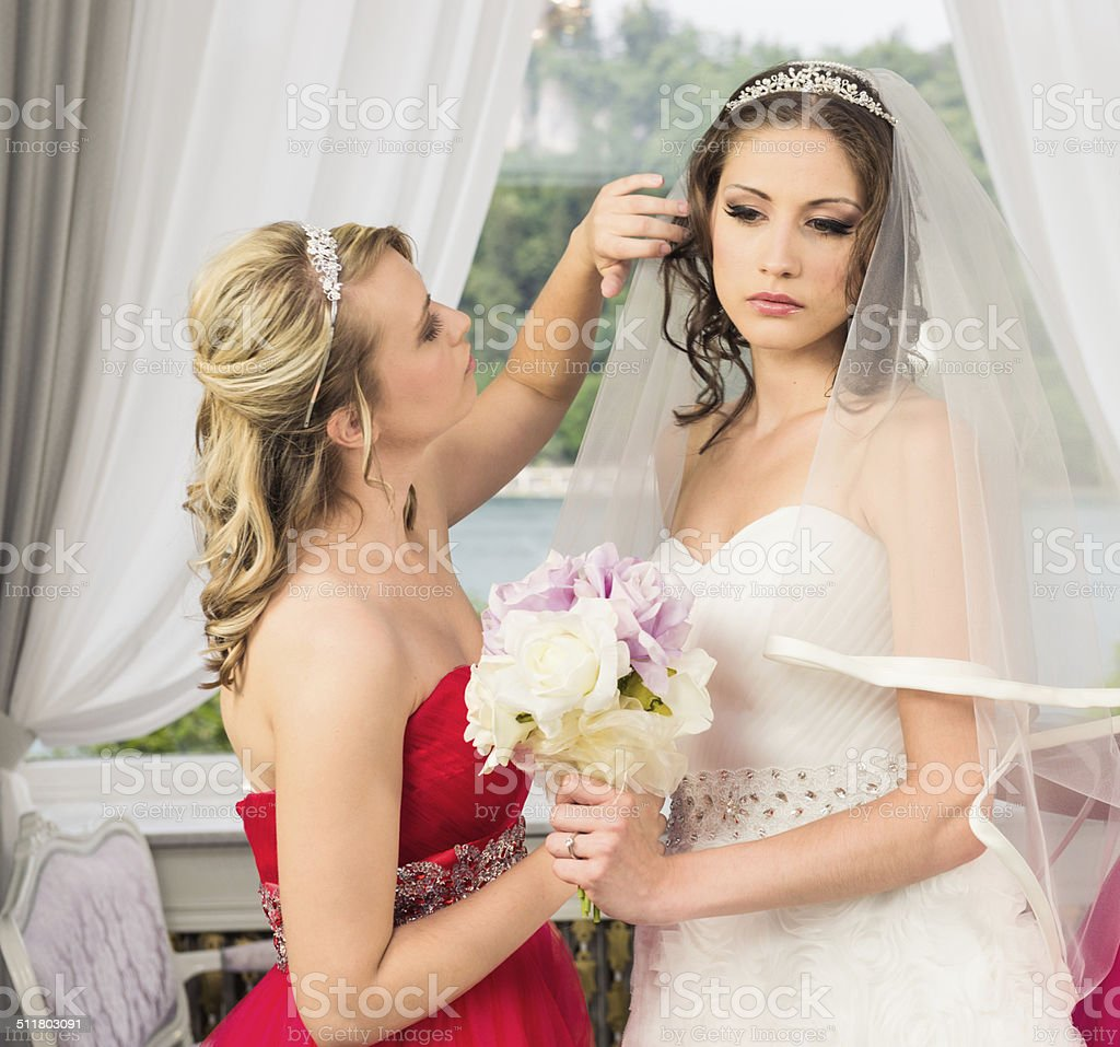Bridesmaid helping the bride to get ready stock photo