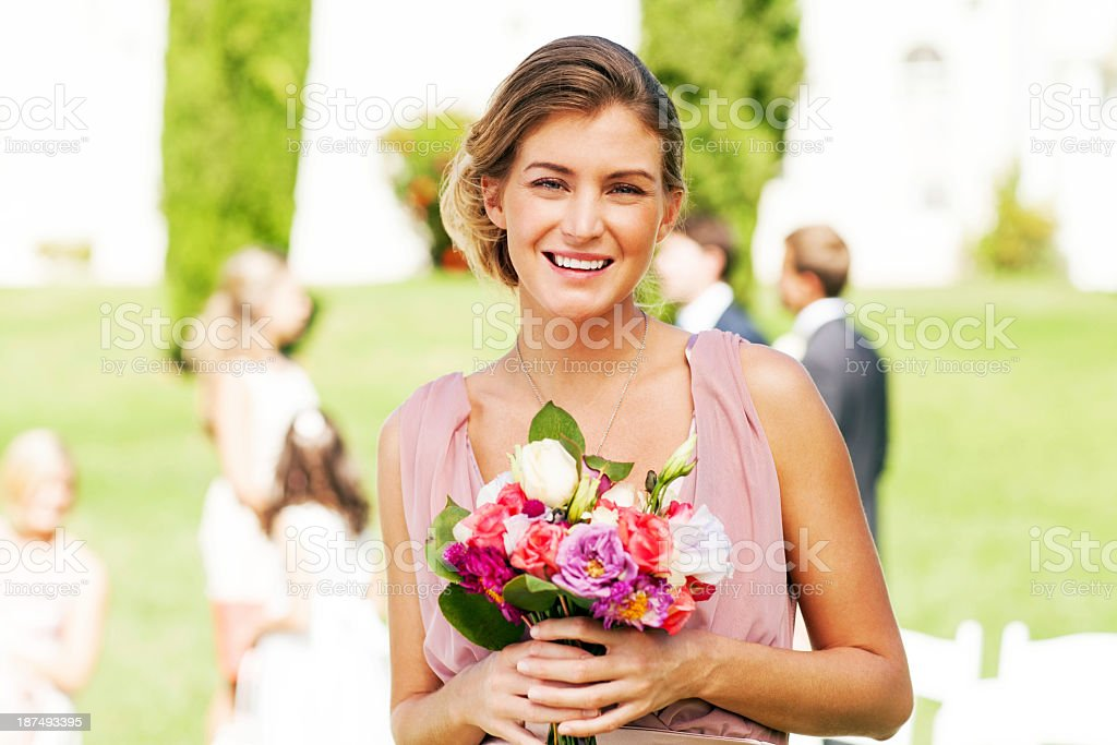 Bridesmaid Holding Bouquet Of Flowers At Garden Wedding stock photo