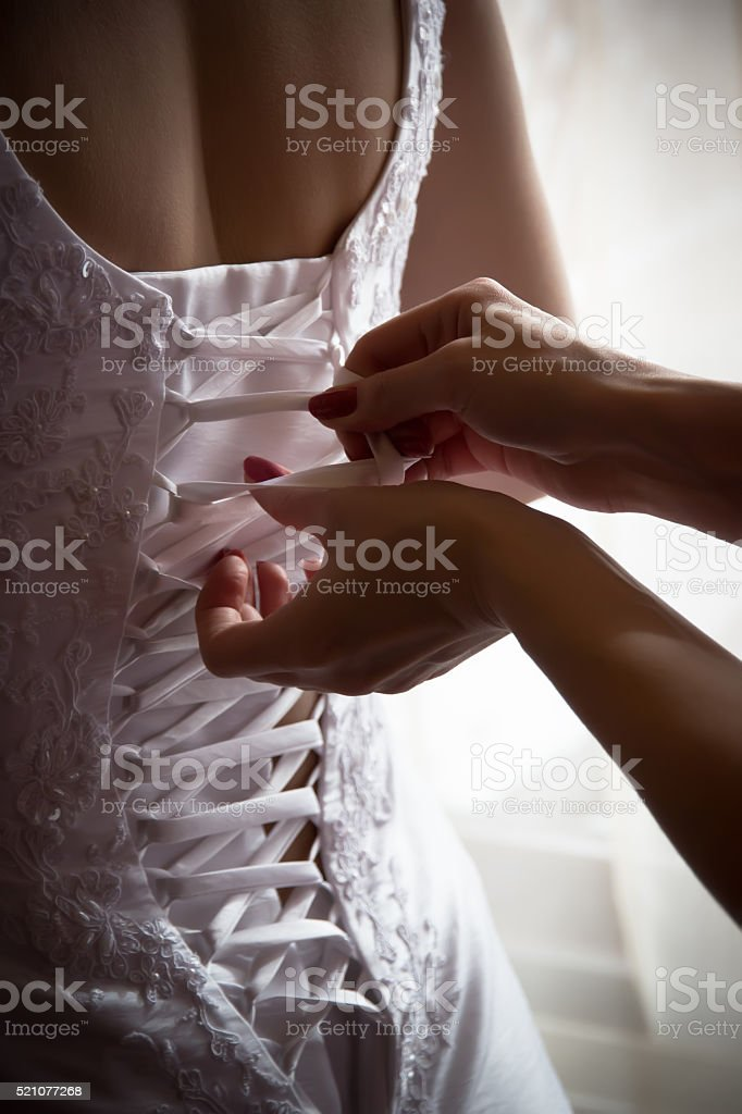 Bridesmaid tie the laces on the wedding dress stock photo