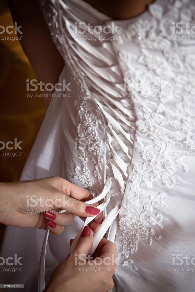 Bridesmaid tie the laces on wedding dress stock photo