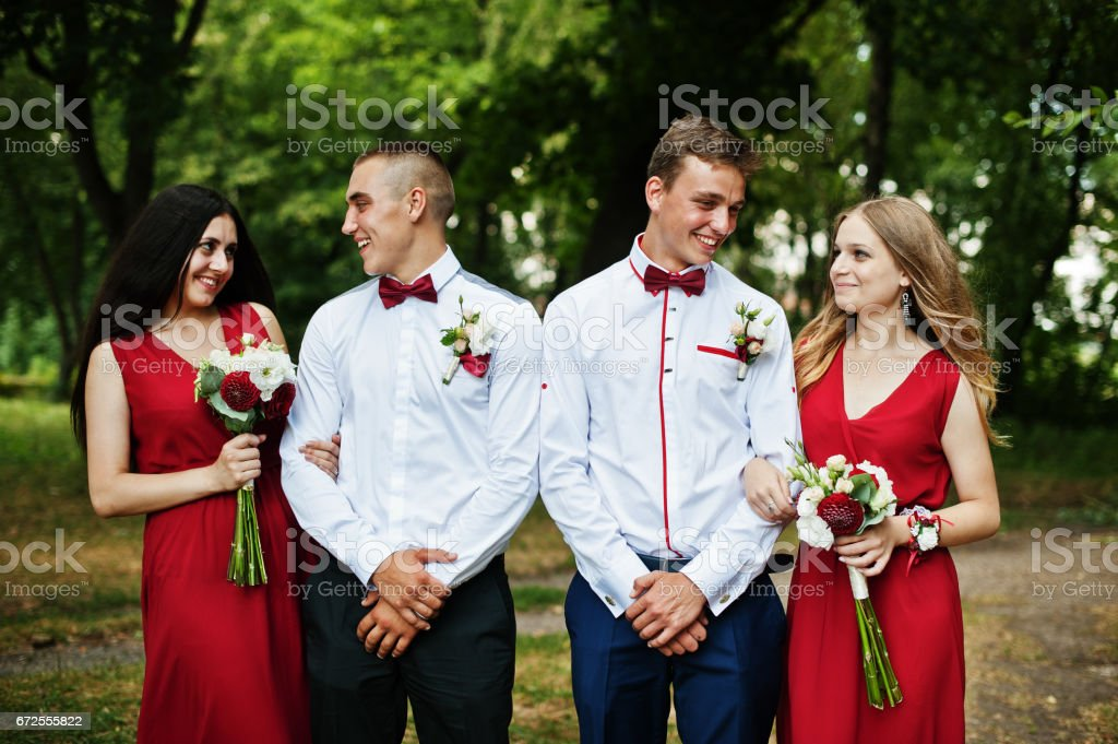Bridesmaids at red dresses with groomsman or best man at wedding. stock photo