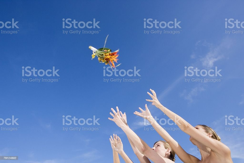 Bridesmaids catching wedding bouquet stock photo