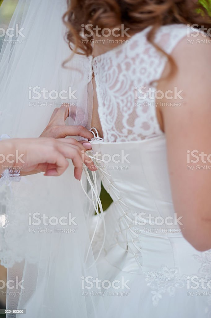 bridesmaids helps to bride dress in wedding morning stock photo