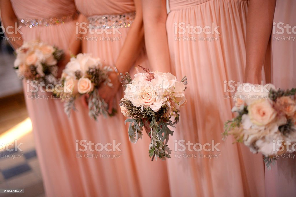 Bridesmaids holding beautiful bridal bouquets stock photo