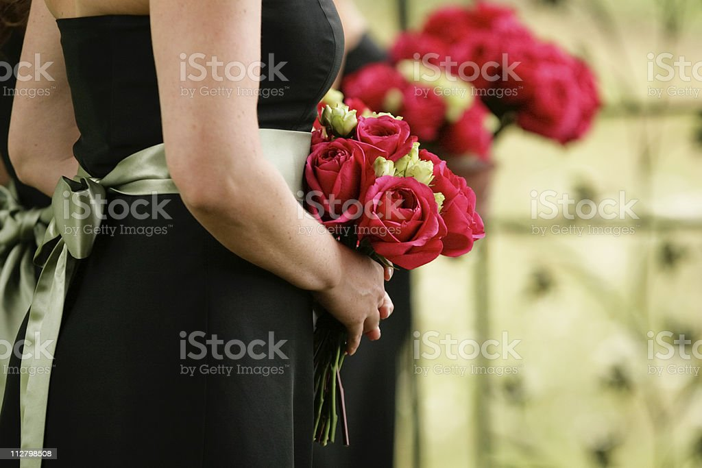 Bridesmaids holding flowers in row at wedding ceremony royalty-free stock photo