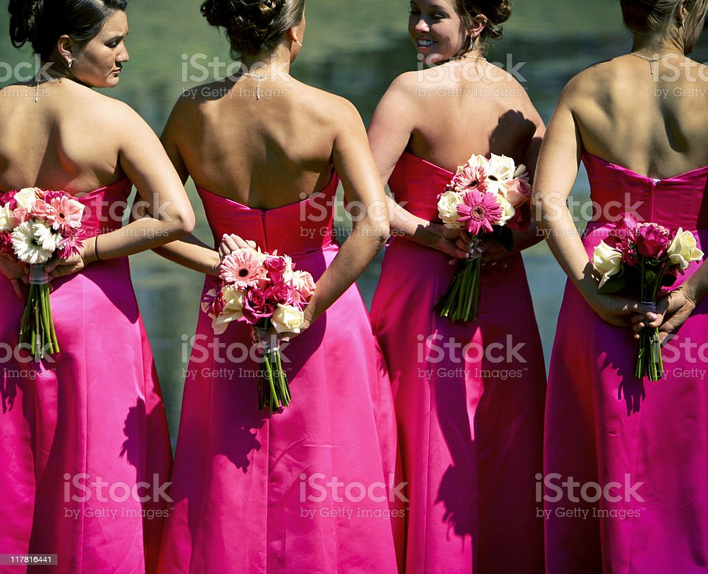 Bridesmaids in fuchsia pink gowns with flowers behind back stock photo
