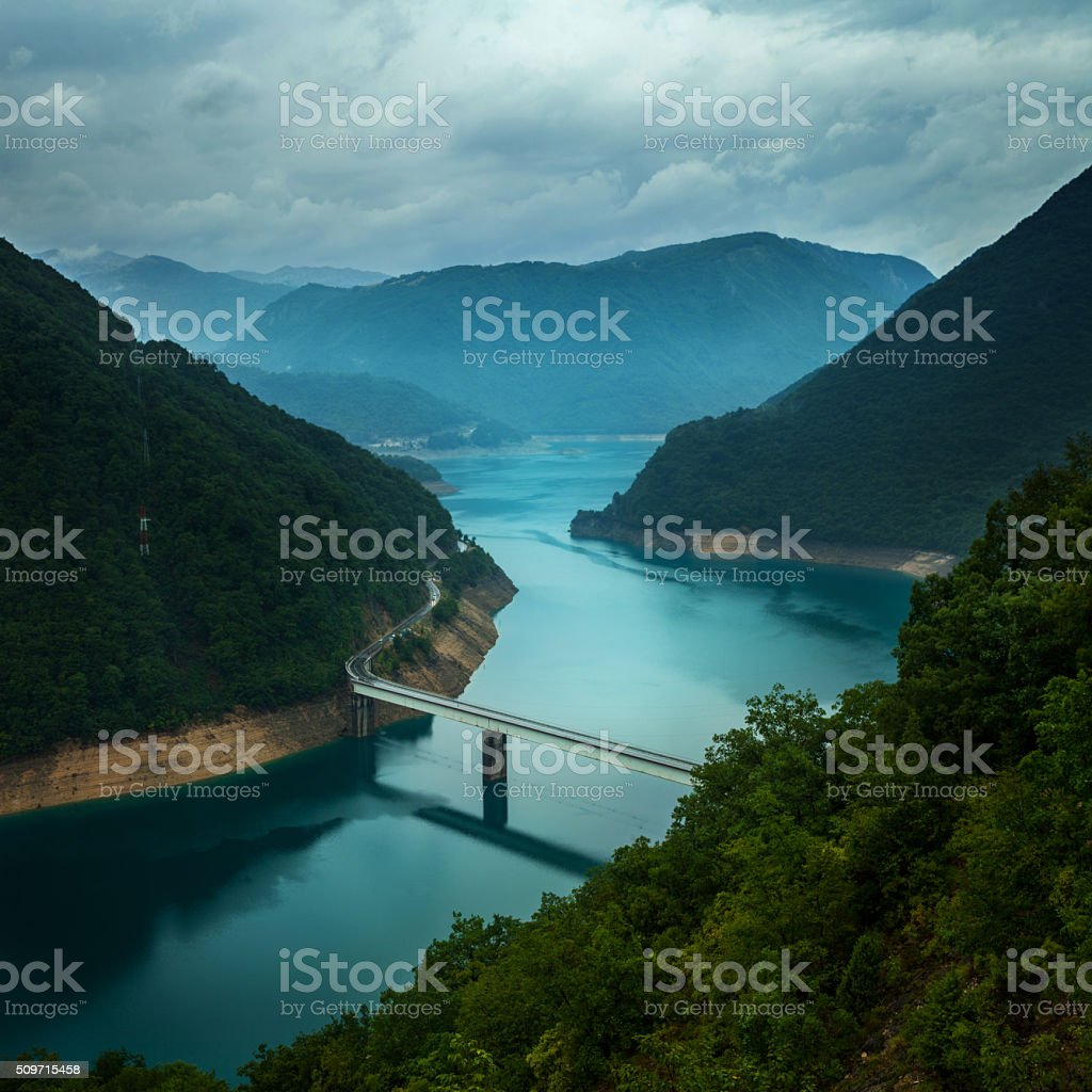 Bridge across the beautiful Pivska lake and mountains of Durmitor stock photo