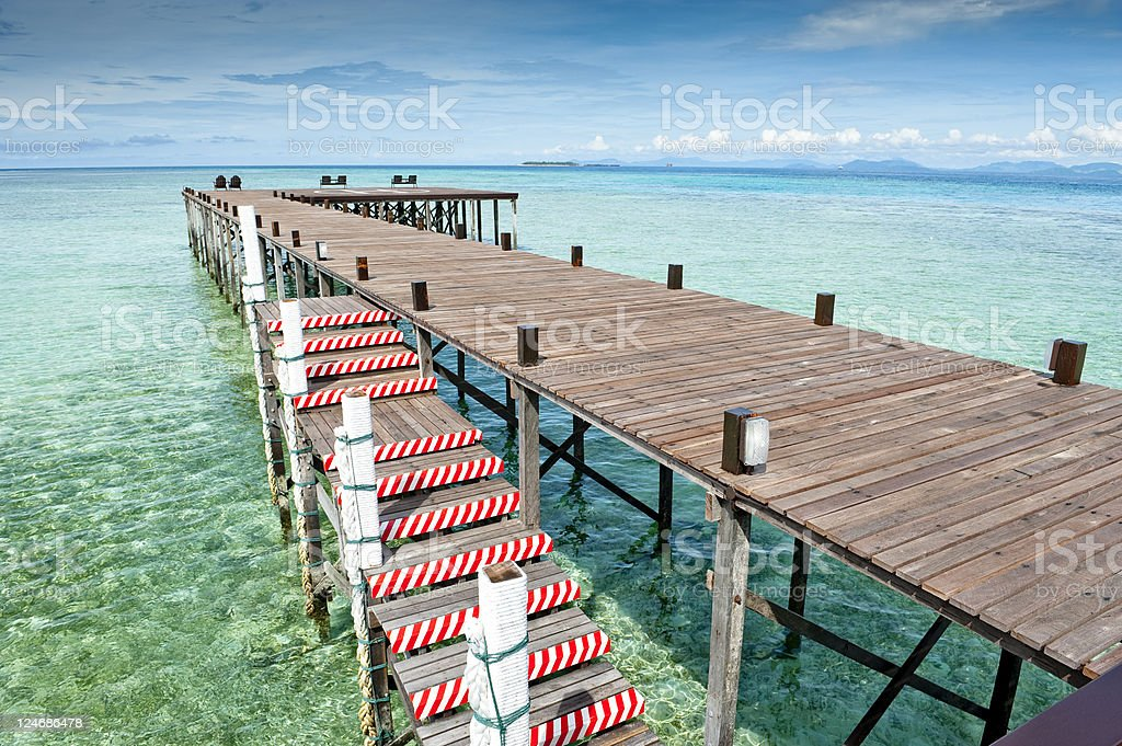 Bridge into sea under clear blue sky stock photo