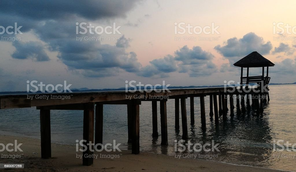bridge into sea under cloudy sky stock photo