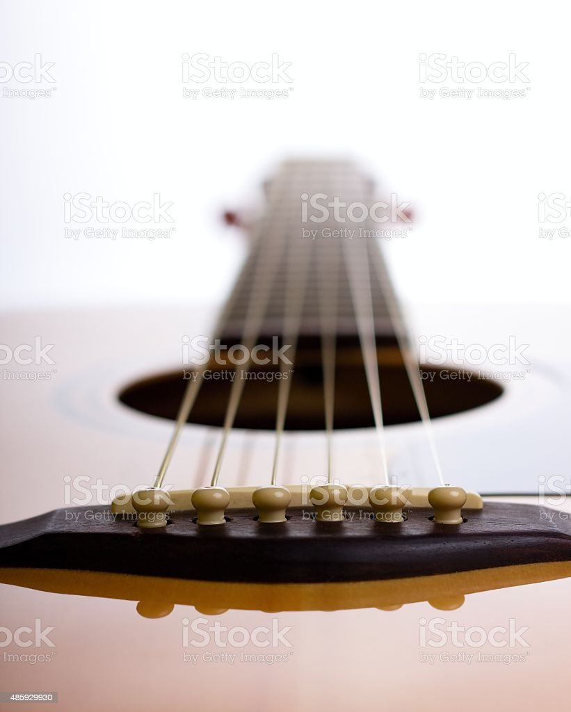 Bridge of acoustic guitar against light stock photo