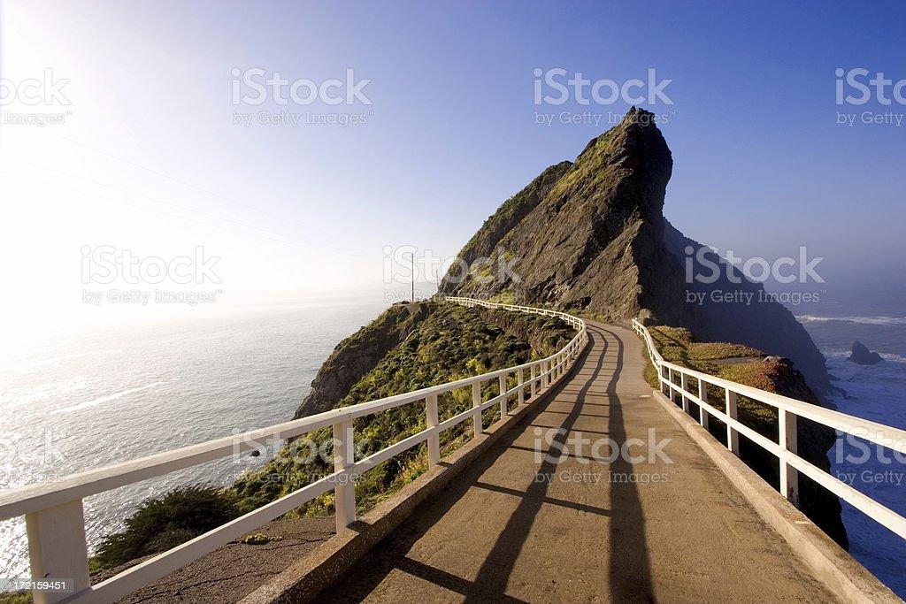 Bridge on a mountain with blue ocean all around stock photo