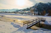 bridge over a small creek, winter in the village,
