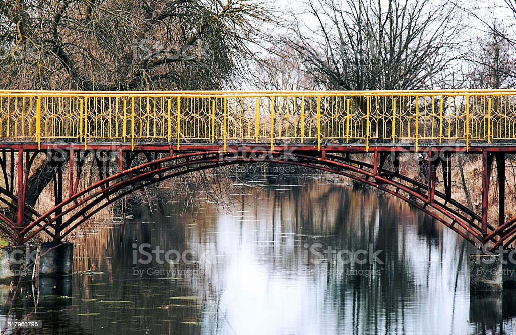 bridge over a small river with yellow railing stock photo