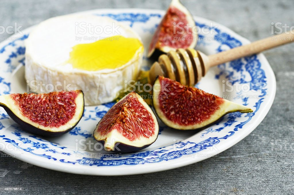 Brie cheese, honey and fig on blue ceramic plate stock photo