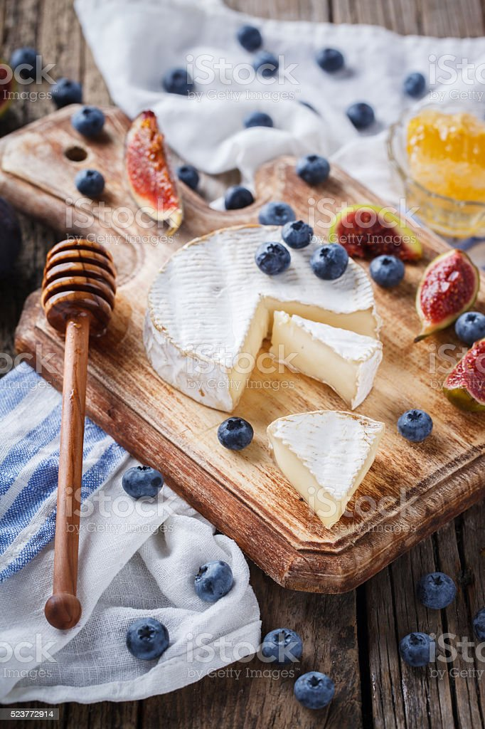 Brie cheese,Camembert with figs,blueberries and honey stock photo