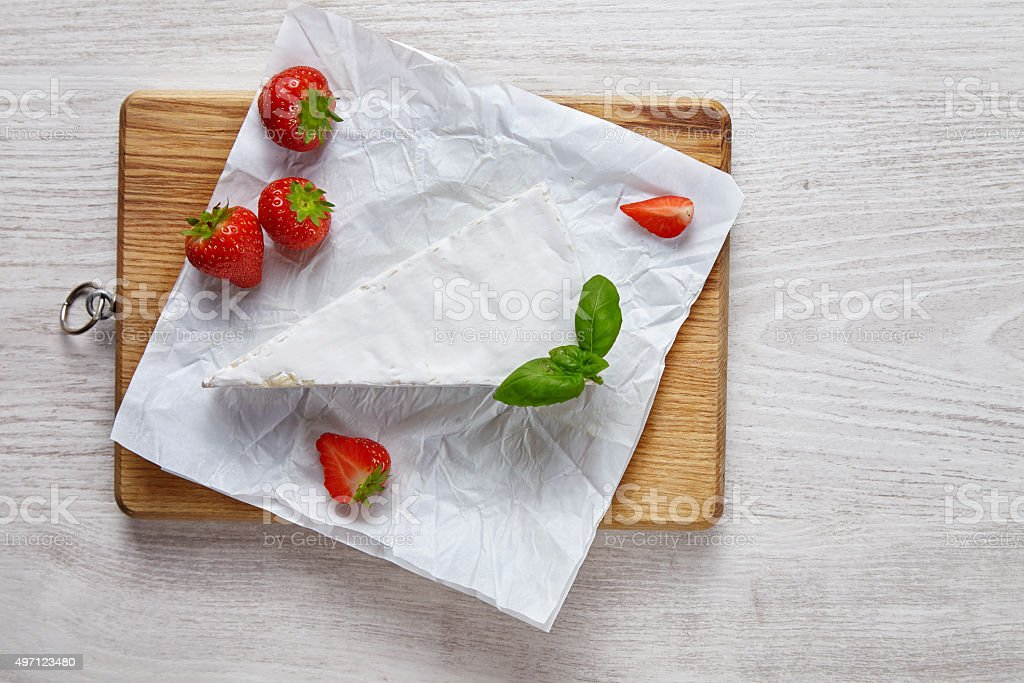 Brie uncovered on wooden plate on white table with strawberries stock photo