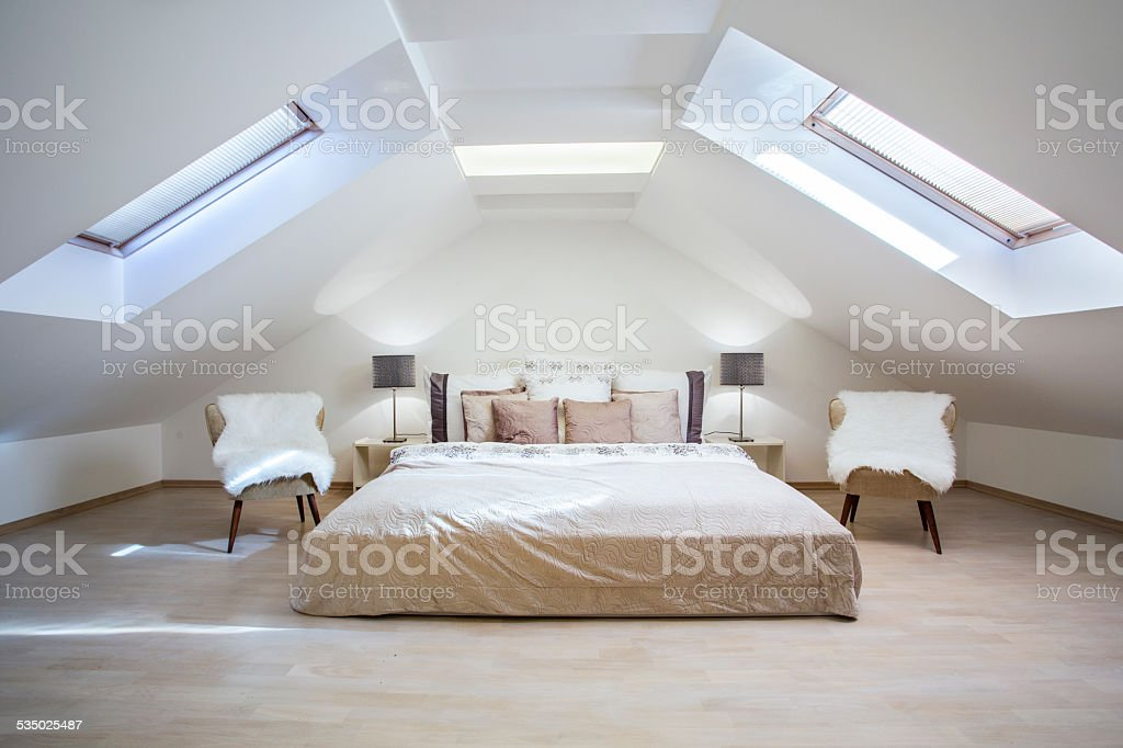 Bright attic bedroom in the apartment stock photo