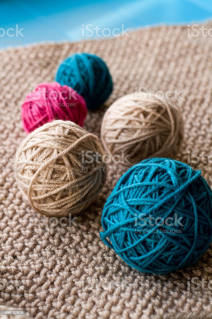Bright balls of yarn lying on beige knitted plaid stock photo