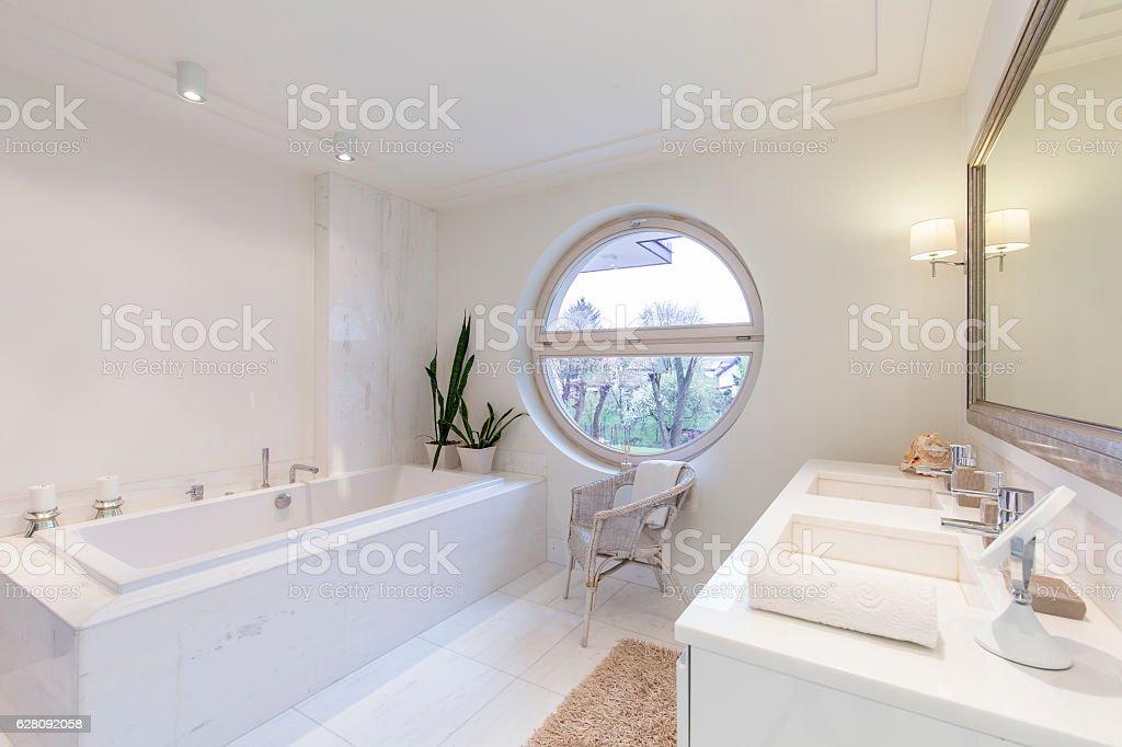 Bright bathroom with round window stock photo