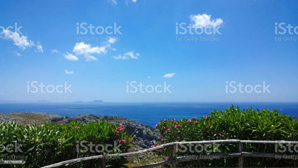 Bright beautiful panoramic views of the Libyan (Mediterranean) sea on the southern coast of Crete from the monastery of Preveli. Spring flowering bushes and fence in the foreground stock photo