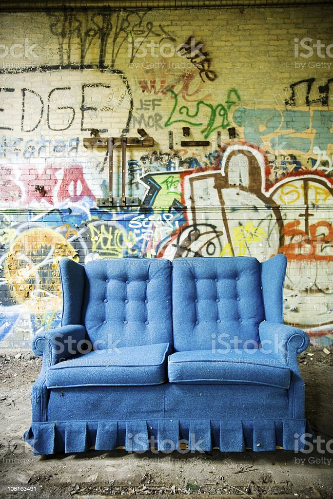 Bright Blue Couch Against Cement Wall of Graffiti royalty-free stock photo