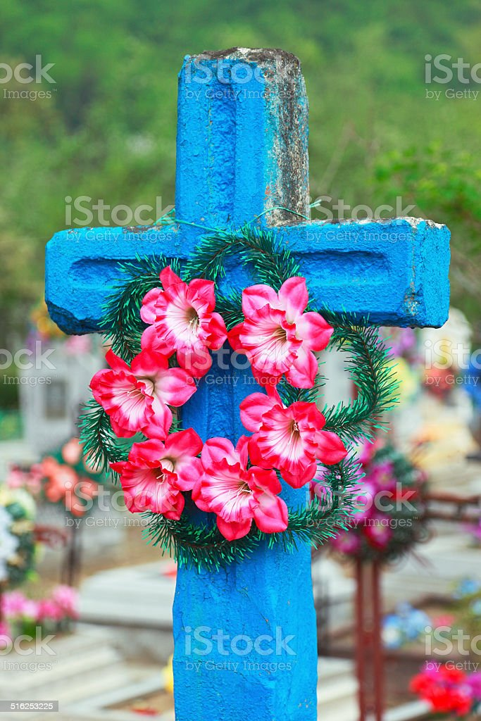 Bright blue cross with pink artificial flowers stock photo
