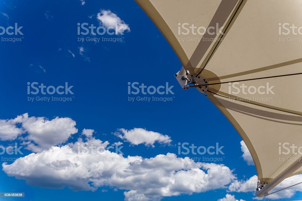 bright blue sky with clouds and umbrella stock photo