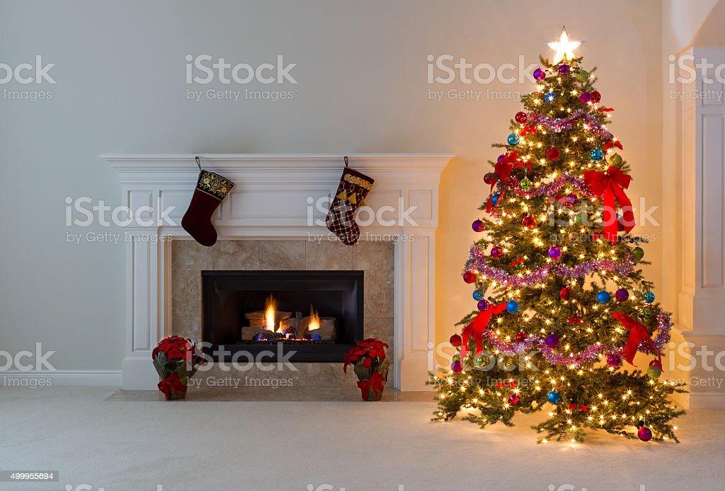 Bright Christmas tree with burning fireplace stock photo